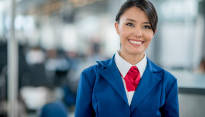 Friendly flight attendant smiling at the airport